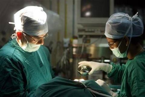 Patient plays guitar on operation table while undergoing brain surgery